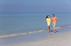 Pares do homem & da mulher que funcionam em uma praia vazia Fotos de Stock Royalty Free