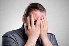 Pares do homem através de seus dedos Fotografia de Stock