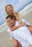Pares do homem e da mulher que têm o divertimento em uma praia Fotos de Stock Royalty Free