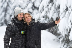 Pares do homem novo que tomam a foto de Selfie na neve Forest Outdoor Guys Holding Hands foto de stock