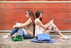 Pares do moderno de amigas no momento do desinteresse com telefones fotografia de stock royalty free