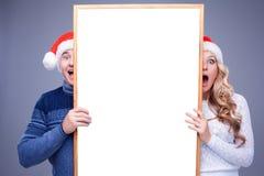 Pares do Natal que guardam a placa branca com vazio imagem de stock