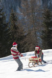 Pares do Natal que jogam com os presentes na neve Imagem de Stock