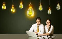 Pares do negócio com bulbos da ideia Foto de Stock Royalty Free