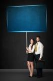 Pares do negócio com placa azul Fotografia de Stock