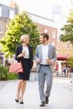 Pares do negócio que andam através do parque com café afastado Imagens de Stock Royalty Free