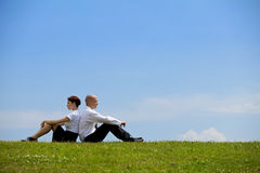 Pares do negócio que sentam-se de volta à parte traseira na grama Foto de Stock Royalty Free