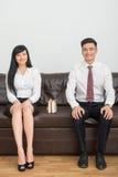Pares do negócio que sentam-se no sofá no escritório Fotografia de Stock
