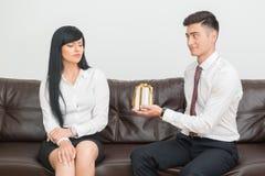 Pares do negócio que sentam-se no sofá no escritório Imagens de Stock Royalty Free