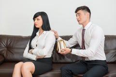Pares do negócio que sentam-se no sofá no escritório Fotos de Stock