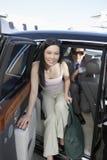 Pares do negócio que obtêm abaixo de um carro no aeródromo Fotografia de Stock Royalty Free