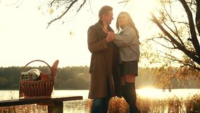 Pares do outono Pares bonitos na roupa morna que está perto do lago, onde refletido o céu do outono, desvanecido, piquenique vídeos de arquivo