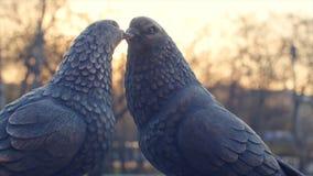 Pares do pombo branco do vintage feito do fundo do bronze e do sol pombos das estatuetas feitos do metal Duas estatuetas de Imagens de Stock