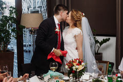 Pares do recém-casado que beijam no copo de água no restaurante, brid fotos de stock royalty free