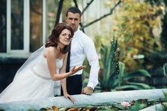 pares do recém-casado que levantam perto da fonte rústica imagem de stock royalty free