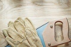 Pares do serrote afiado de couro das luvas protetoras na placa de madeira fotos de stock
