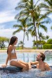 Pares do spa resort que relaxam apreciando a piscina da banheira de hidromassagem do Jacuzzi fora na fuga da lua de mel dos feria fotografia de stock royalty free