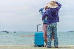 Pares doces que abraçam-se com bagagem azul moderna do curso na praia Foto de Stock Royalty Free