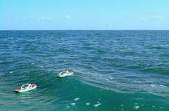 Pares dos flip-flops brancos na água Foto de Stock Royalty Free