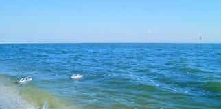 Pares dos flip-flops brancos na água Fotos de Stock
