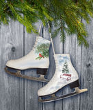 Pares dos patins de gelo brancos com decoração do inverno - backrround, cartaz fotos de stock royalty free