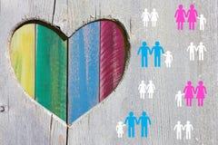 Pares e famílias do gay e lesbiana no fundo de madeira com coração multicolorido do arco-íris fotografia de stock royalty free