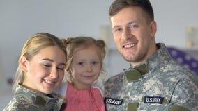 Pares e filha militares de sorriso que olham a câmera, orgulho nacional, patriotismo filme