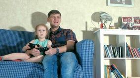 Pares e filha que jogam no jogo de vídeo em sua sala de visitas video estoque