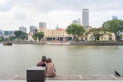 Pares e pombo pelo rio de Singapura no fim da tarde Imagem de Stock