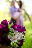 Pares e ramalhete grávidos das flores no primeiro plano imagens de stock royalty free