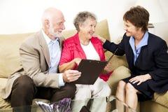 Pares e Saleswoman sênior fotografia de stock royalty free