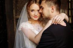 Pares elegantes de la boda que abrazan en patio viejo en stre europeo Foto de archivo libre de regalías