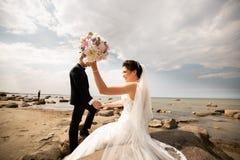Pares elegantes de la boda que se colocan en orilla de mar Los recienes casados est?n caminando por el mar fotos de archivo