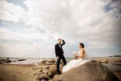 Pares elegantes de la boda que se colocan en orilla de mar Los recienes casados est?n caminando por el mar imagenes de archivo
