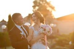 Pares elegantes de los recienes casados felices que presentan en el parque en su día de boda Novia perfecta de los pares, broma d fotos de archivo