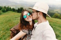 Pares elegantes del inconformista que viajan y que se besan y que ríen en t Foto de archivo libre de regalías