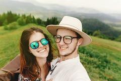 Pares elegantes del inconformista que viajan y que sonríen encima de la montaña Fotografía de archivo
