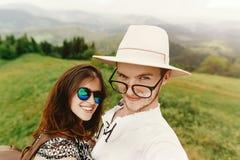 Pares elegantes del inconformista que viajan y que sonríen encima de la montaña Fotos de archivo
