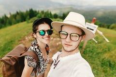 Pares elegantes del inconformista que viajan y que sonríen encima de la montaña Fotos de archivo libres de regalías