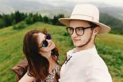 Pares elegantes del inconformista que viajan y que sonríen encima de la montaña Foto de archivo