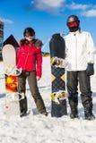 Pares elegantes en trajes de esquí, cascos y gafas del esquí que colocan los wi Imagen de archivo