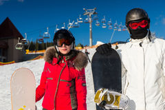 Pares elegantes en trajes de esquí, cascos y gafas del esquí que se colocan con Imagenes de archivo