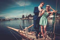 Pares elegantes en un yate de lujo Fotografía de archivo libre de regalías