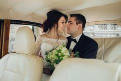 Pares elegantes felices del recién casado que presentan en coche retro Fotos de archivo libres de regalías