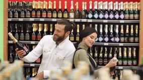 Pares elegantes felizes que escolhem o vinho junto ao estar na loja de vinhos video estoque
