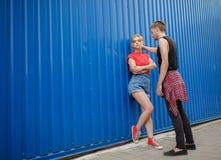Pares elegantes modernos jovenes en fondo azul, adolescentes soleados de los inconformistas de los pares del retrato Fotografía de archivo libre de regalías