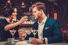 Pares elegantes que comen el desierto y el café junto en un restaurante Fotografía de archivo