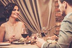 Pares elegantes que disfrutan de la comida en el restaurante Imagenes de archivo