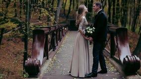 Pares elegantes que estão na ponte que guarda as mãos, beijando filme
