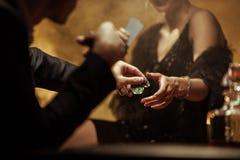 Pares elegantes que jogam o pôquer e que compartilham de microplaquetas do casino foto de stock royalty free